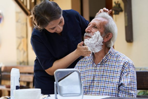 Lady taking care of elderly man at home